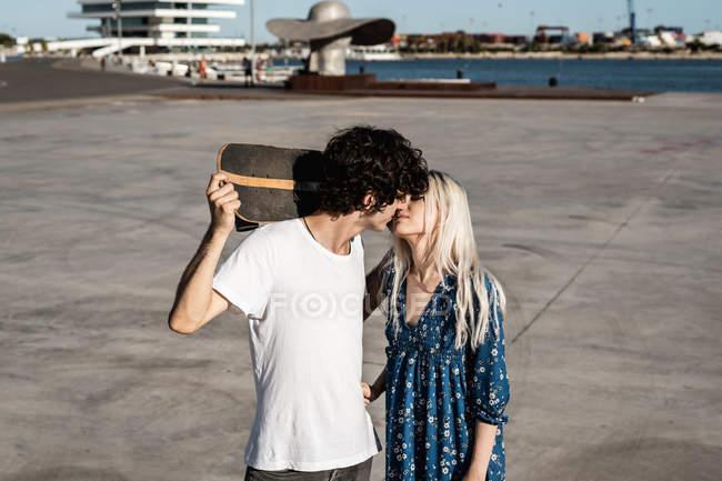Attraente giovane coppia di stilisti che si abbracciano e si baciano per strada mentre l'uomo in camicia bianca tiene lo skateboard — Foto stock