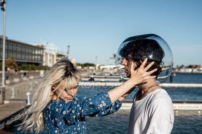 Attractive unhappy blond female touching transparent round aquarium on head of adult dark haired man — Photo de stock