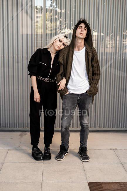 Vista laterale di coppia alla moda che si sostengono a vicenda mentre la donna si appoggia sul fidanzato contro la parete a strisce dell'edificio moderno — Foto stock
