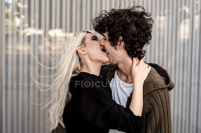 Жінка кусається за язик і торкається шиї молодого кучерявого темного волосся чоловіка стоячи і цілуючись — стокове фото