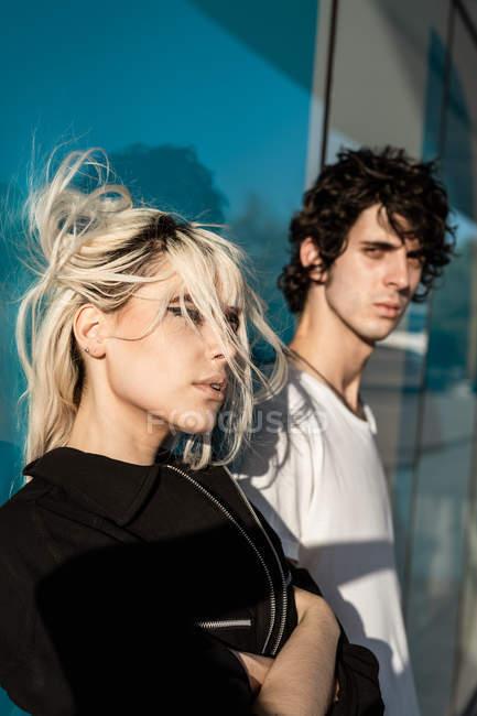Mulher em roupas pretas em pé ao lado de homem alto, enquanto em pé contra a parede azul com reflexo de rua à luz do sol — Fotografia de Stock