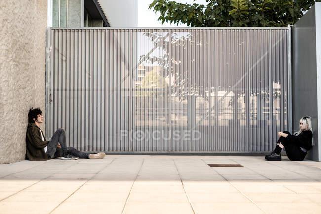 Вид сбоку несчастная одинокая женщина и мужчина сидят напротив друг друга на земле, опираясь на стену — стоковое фото