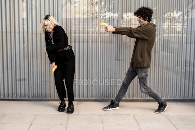 Cheerful man aiming with banana at woman protecting with hands and laughing while having fun together on street — Stock Photo