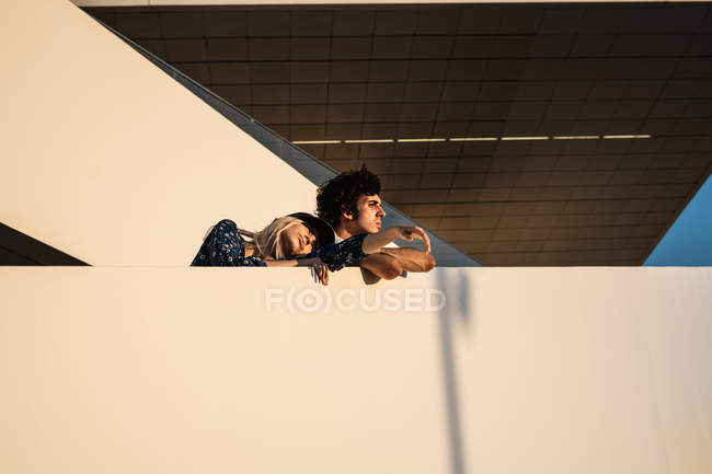 Mulher loira de chapéu e orgulhoso homem de cabelos escuros com braços cruzados olhando para longe nas escadas — Fotografia de Stock