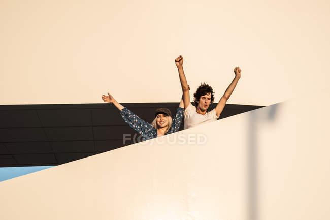 Fröhliches Paar, das die Arme hebt, wegschaut und den Blick vom Treppenhaus schweifen lässt — Stockfoto