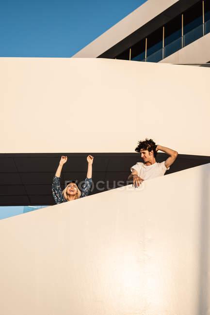 Von unten ein fröhliches Paar, das die Arme hebt, wegschaut und den Blick vom Treppenhaus schweifen lässt — Stockfoto