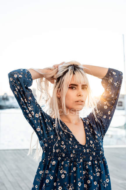 Gorgeous pensive blond female looking at camera with curiosity while standing and touching hair on street during sunset — Stock Photo