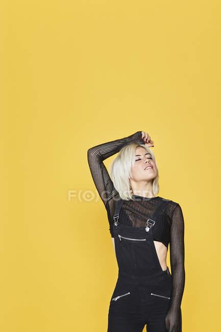 Attraente bionda in tute nere in piedi e guardando con gli occhi chiusi su sfondo giallo — Foto stock