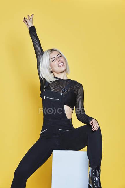Attraktive stilvolle Frau in schwarzen Overalls sitzt auf weißem Kasten und macht Friedensgeste auf gelbem Hintergrund — Stockfoto