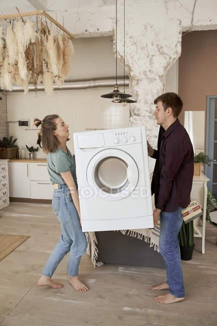 Vue latérale de l'homme et de la femme pieds nus portant une machine à laver tout en déménageant dans une nouvelle maison — Photo de stock