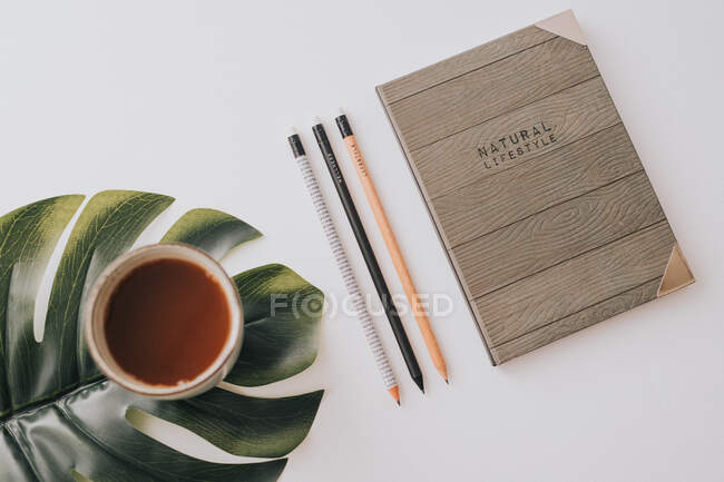 From above stylish notebook with wooden cover composed with row of pencils and mug of hot drink on green Monstera leaf on white background — Stock Photo