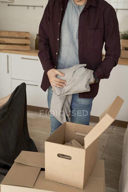 Hombre irreconocible que saca sudor gris suave de las cajas de la cocina. - foto de stock