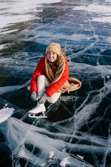 Donna seduta sul fiume ghiacciato e legare i lacci delle scarpe — Foto stock