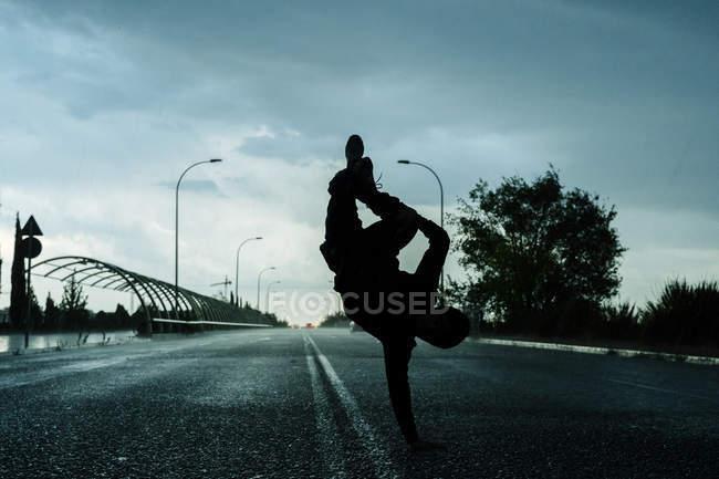 Silhouette einer Tänzerin in Sportkleidung beim Handstand inmitten einer leeren Straße mit bewölktem Himmel und Bäumen im Hintergrund — Stockfoto