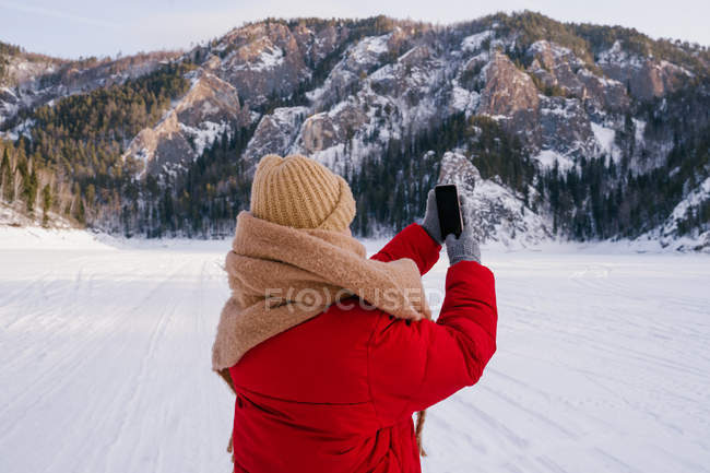 Vue arrière de Femme prenant des photos de montagnes enneigées avec smartphone — Photo de stock