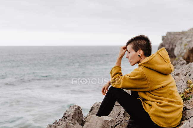 Side view of traveler woman in yellow warm hoodie sitting alone on rocky shore looking at foamy waves on cloudy day — Stock Photo
