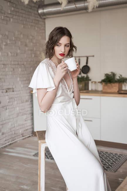 Nachdenkliche Frau im weißen Seidenkleid, die wegschaut und denkt, während sie auf einem Hocker mit weißem Kaffeebecher in der Wohnung sitzt — Stockfoto
