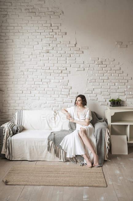 Nachdenkliche erwachsene Frau, die wegschaut und träumt, während sie auf dem Sofa sitzt und Heißgetränk im hellen modernen Wohnzimmer trinkt — Stockfoto