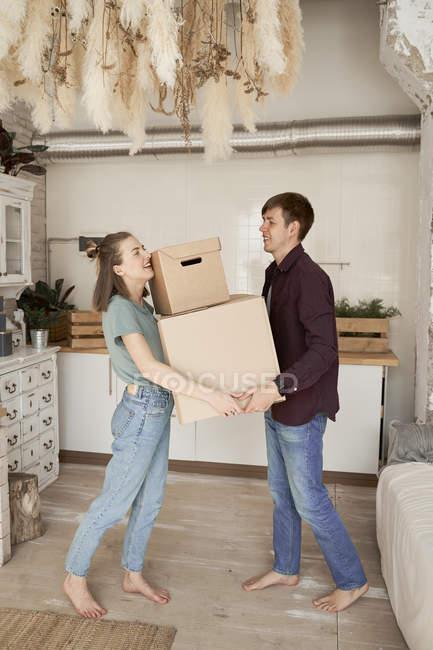 Seitenansicht eines jungen Paares, das sich Mühe gibt und Kartons mit Sachen im Haus trägt — Stockfoto