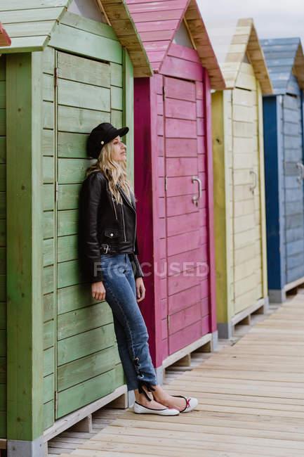 Нахабна жінка в чорній шапці і шкіряній куртці спирається на стіну дерев'яних пляжних хатин. — стокове фото