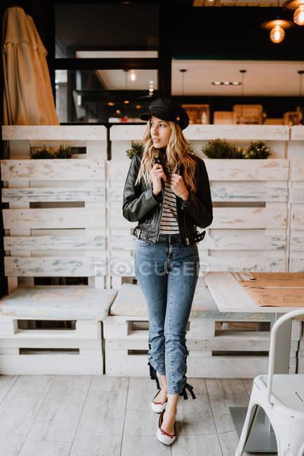 Femme tendance aux cheveux longs vêtue d'une veste et d'une casquette en cuir, allongée sur la table et regardant ailleurs — Photo de stock