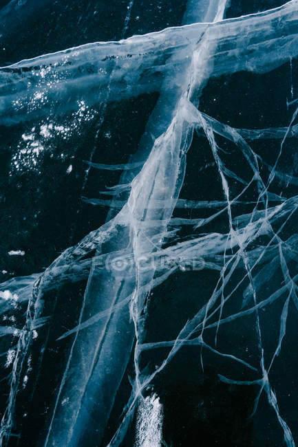Closeup of dark natural ice texture with large cracks on frozen Siberian river on wintertime — Stock Photo