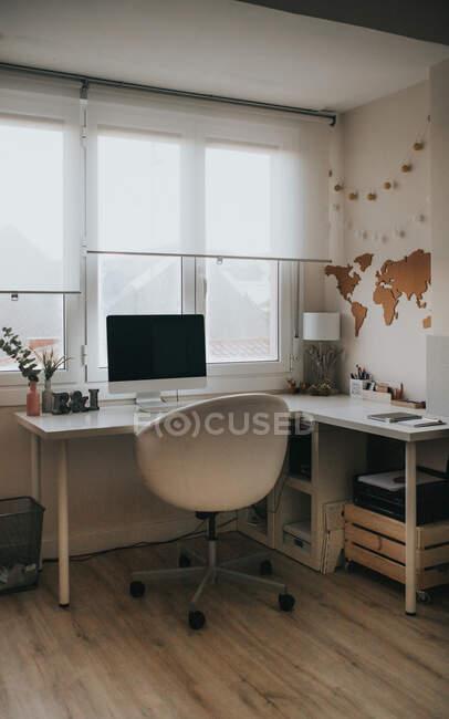 Escritório home leve vazio com laptop na mesa e mapa do mundo decorativo na parede e cadeira confortável para trabalhar — Fotografia de Stock