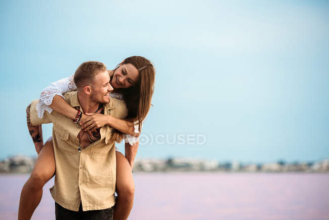 Boyfriend giving piggyback ride to girlfriend on amazing beach of pink water — Stock Photo
