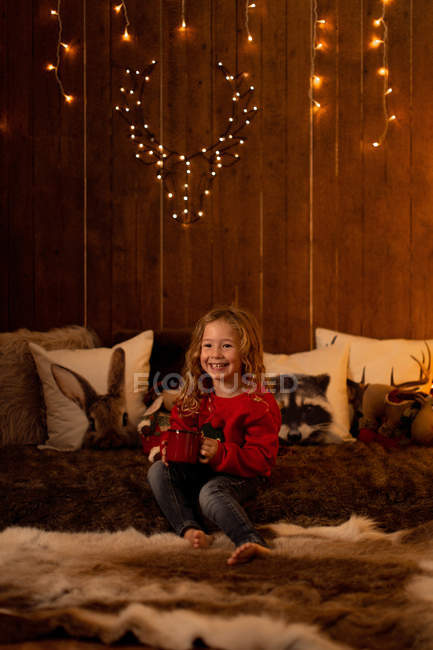 Adorable little girl holding red mug while sitting in room full of Christmas decoration and lights — Stock Photo