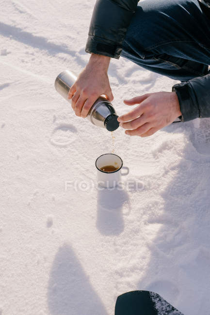 Cropped image of man pouring hot tea from thermos bottle to enamel mug placed on snow during winter trip in Siberia, Russia — Stock Photo