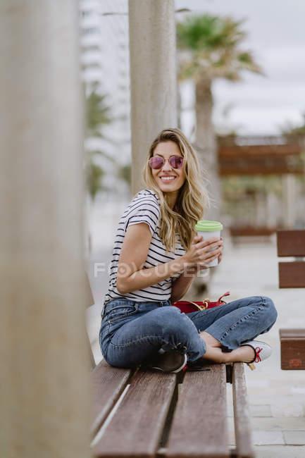 Vista laterale della donna con tazzina da asporto di caffè seduta sulla panchina della città sul lungomare durante la giornata estiva e guardando altrove — Foto stock