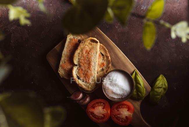 Специи и овощи рядом с тостами на деревянной доске, вид сверху — стоковое фото