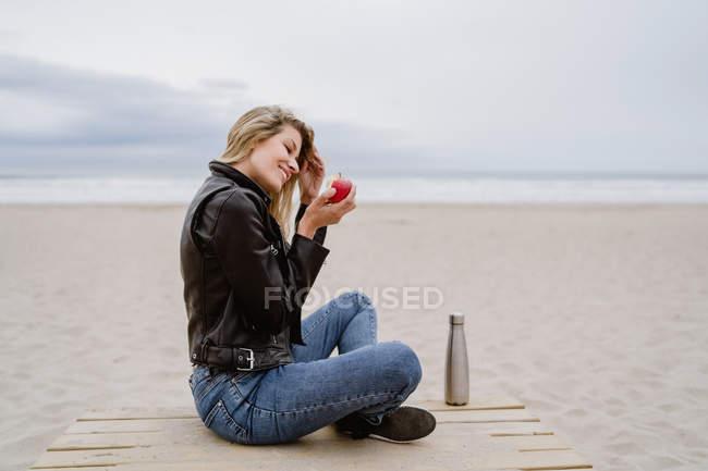 Vista lateral da mulher loira na moda em boné preto e jaqueta de couro comendo maçã madura vermelha na praia — Fotografia de Stock