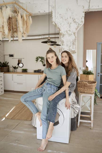 Веселые случайные женщины смеются и сидят на стиральной машине на просторной кухне, развлекаясь дома — стоковое фото
