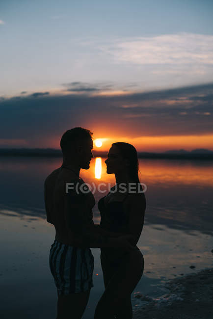 Back view of man and woman on vacation standing in embrace on majestic beach with vibrant crimson sunset sky — Stock Photo