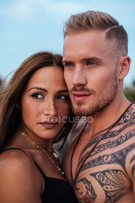 Shirtless tattooed male and sensual woman in swimsuit standing close and looking away with blue sky on background at Spain — Stock Photo