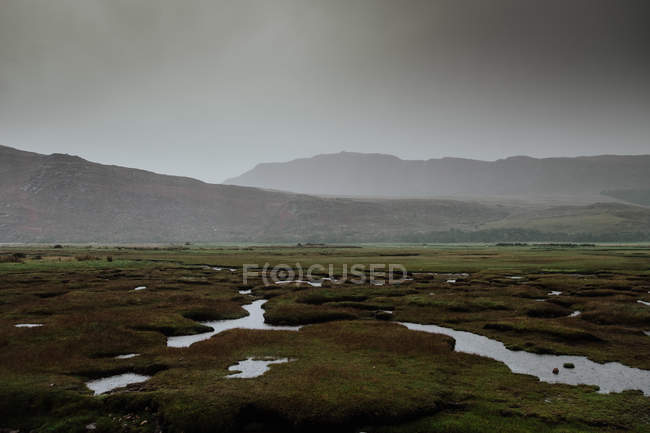 Autumn valley covered with water patches after rain surrounded by foggy hills in Scotland — стокове фото