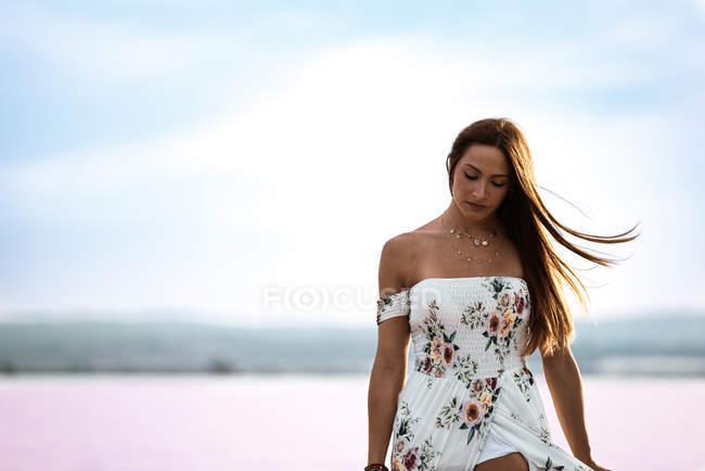 Frau in fließendem, sanftem Kleid im flachen Wasser des exotisch rosa Sees bei Torrevieja in Spanien — Stockfoto