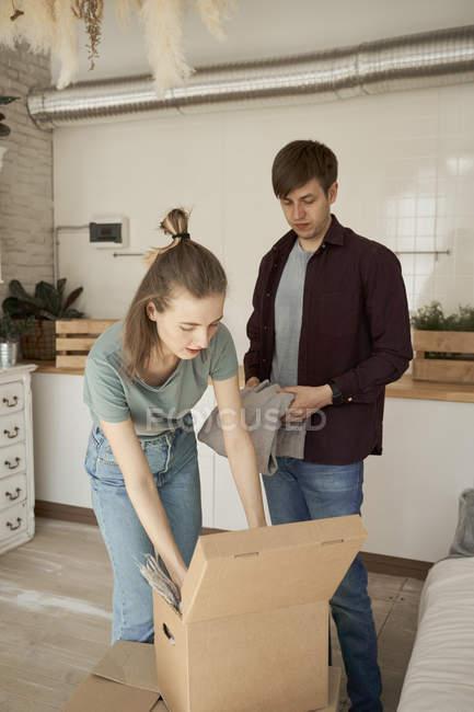Feliz pareja joven sacando sudor gris suave y las cosas de las cajas en la cocina. - foto de stock