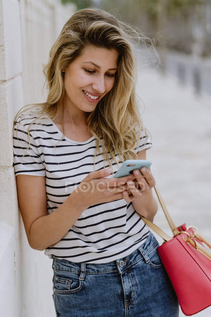 Happy cheerful woman in casual striped shirt and jeans standing next to building on city street and using smartphone — Stock Photo
