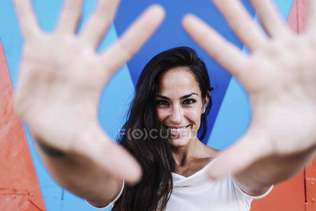 Smiling beautiful woman leaning against a wall while framing the face with hands — Stock Photo