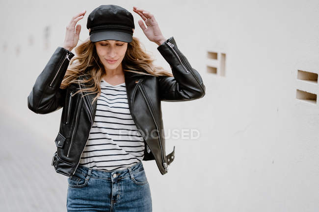 Trendy long haired blonde salope with black cap and jacket with denim confidently looking away while standing near a wall — Photo de stock