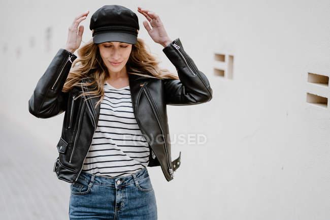 Loira cabelo longo Trendy em tampa preta e jaqueta com denim confiantemente olhando para longe, enquanto está perto de uma parede — Fotografia de Stock