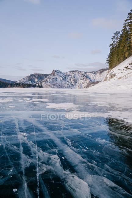 Замерзший речной лед с трещинами — стоковое фото