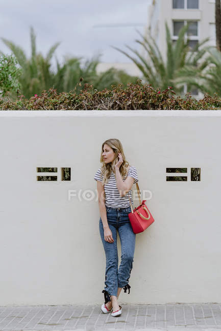 Affascinante donna con tracolla rossa che indossa camicia a righe e jeans in piedi e distogliendo lo sguardo — Foto stock