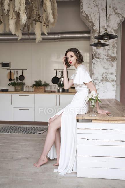 Attraktive junge nachdenkliche Frau mit roten Lippen im weißen Kleid, die wegschaut und nachdenkt — Stockfoto