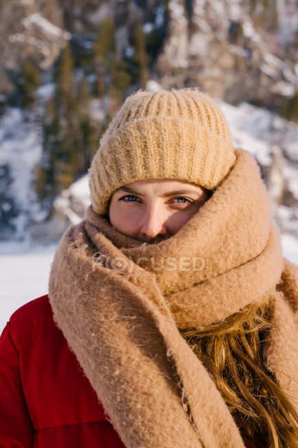 Молодая активная женщина в красной куртке и вязаной бежевой шляпе, завернутая в длинный шерстяной шарф, стоящий рядом со снежными горами — стоковое фото