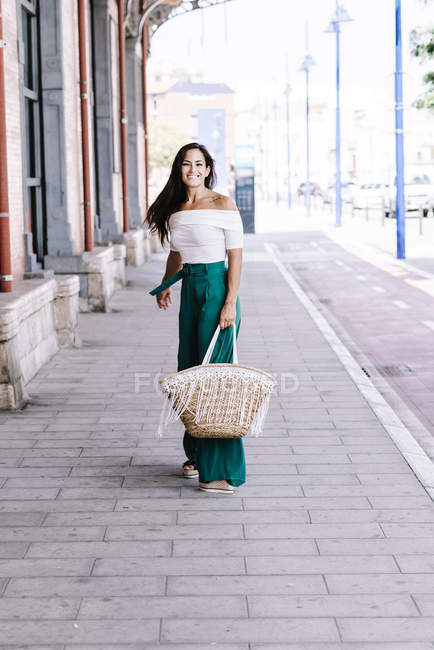Young happy trendy woman walking in city with bag — Stock Photo