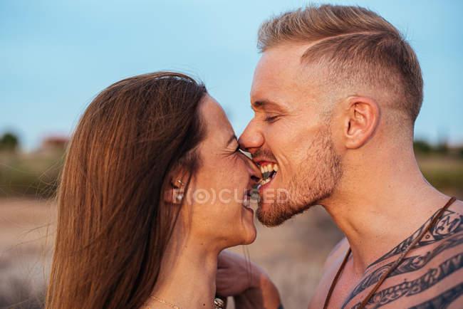 Torse nu tatoué mâle mordant nez de femme avec ciel bleu sur fond en Espagne — Photo de stock