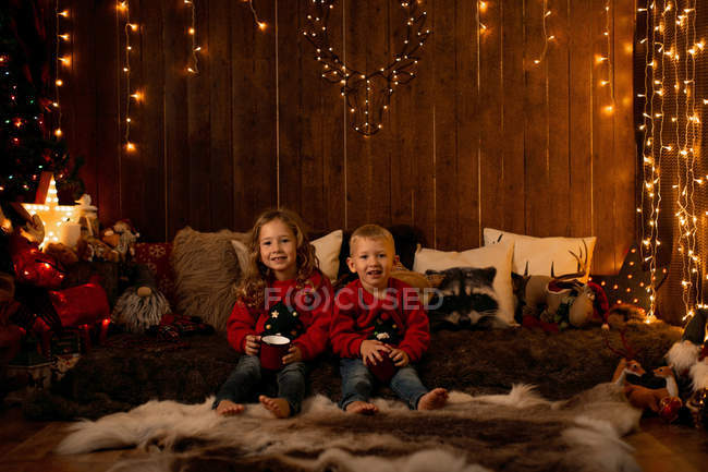 Adorable little girl and boy sitting in room full of Christmas decoration, looking in camera — Stock Photo
